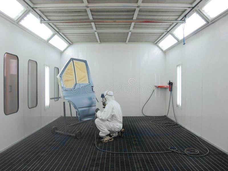 El pintor trabaja en una cabina de aerosol foto de archivo libre de regalías