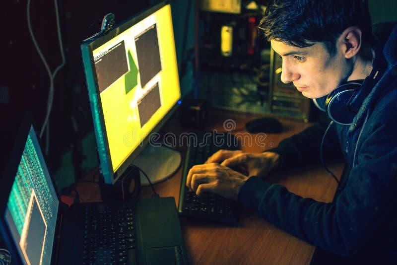 El pirata informático joven en la oscuridad infecta los ordenadores y los sistemas fotografía de archivo libre de regalías