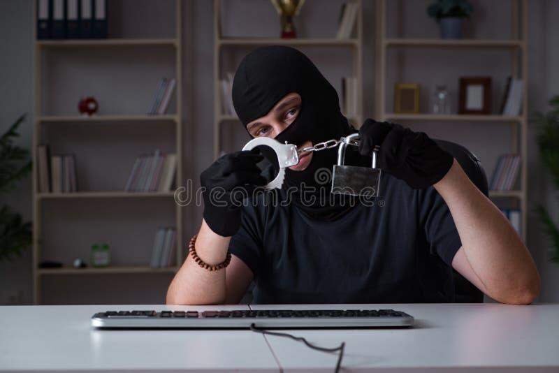 El pirata informático que corta el ordenador tarde en la noche fotos de archivo