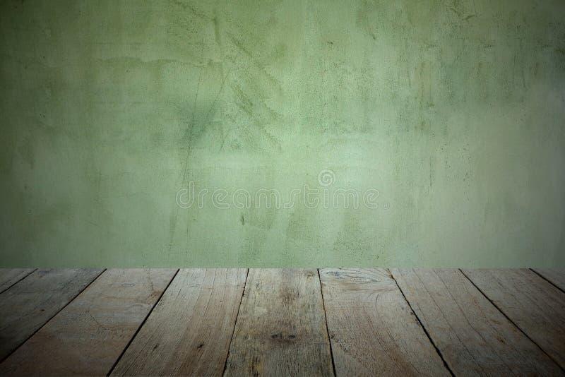 El piso de madera viejo del tablón en el frente para la exhibición del producto y el fondo es la pared vieja del cemento foto de archivo