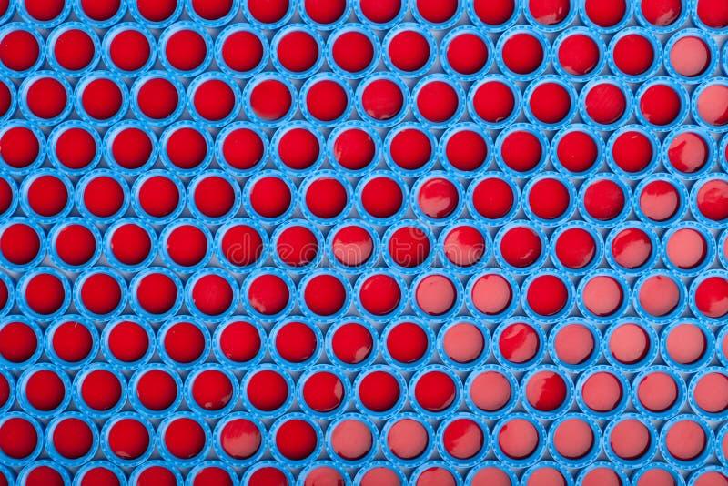 El plástico azul y rojo capsula el fondo fotos de archivo