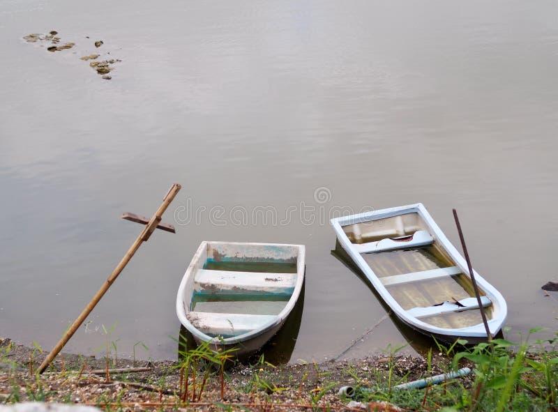 El plástico resistido viejo se descolora hacia fuera los barcos del color en superficie lisa del agua fotos de archivo libres de regalías