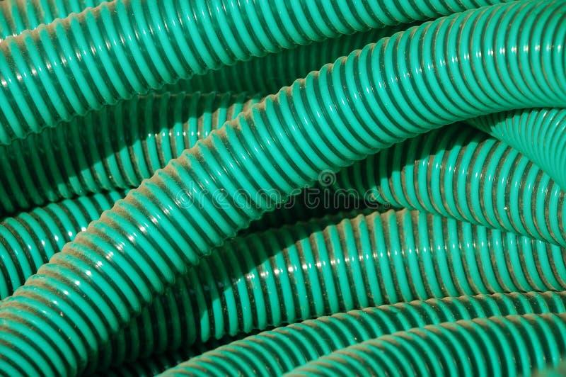 El plástico verde instala tubos el fondo foto de archivo