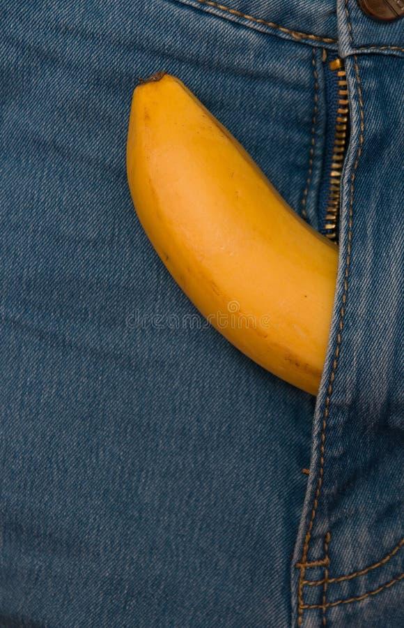 El plátano amarillo se pega fuera de un espacio azul de la copia de los vaqueros de los pantalones de la cremallera fotografía de archivo