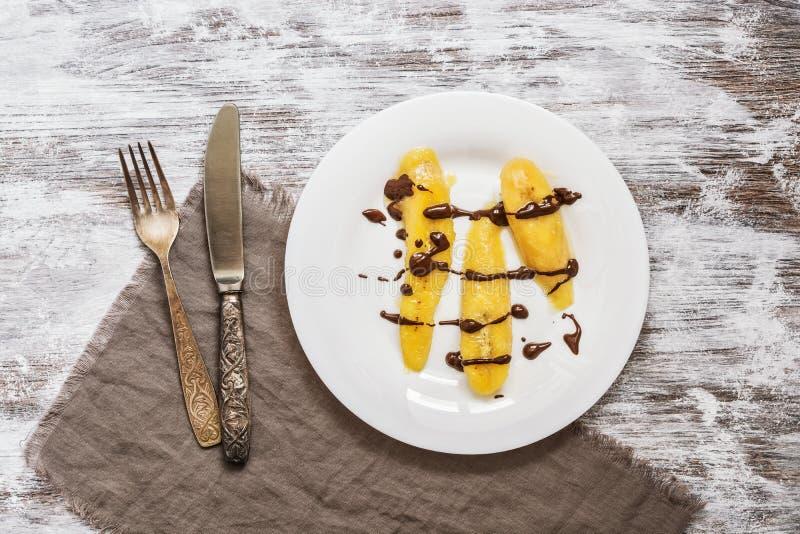 El plátano frito vertió con el chocolate líquido servido en una placa blanca Postre del plátano en fondo blanco rústico imágenes de archivo libres de regalías