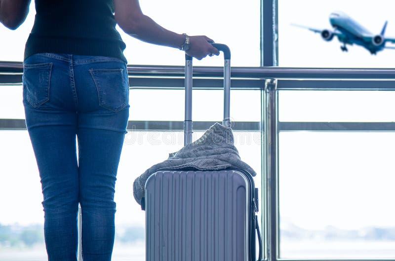 El plan y la mochila de la mujer del viajero consideran el aeroplano en la ventana de cristal del aeropuerto, el bolso tur?stico  foto de archivo libre de regalías
