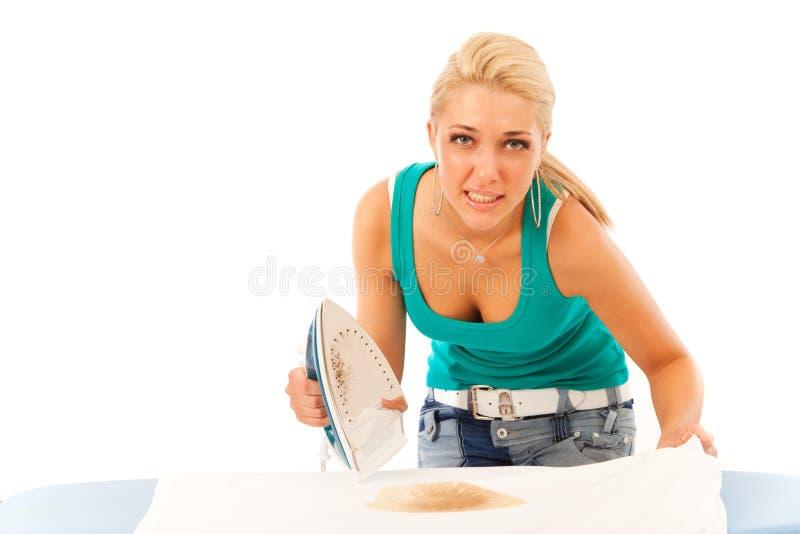 El planchar de la mujer joven fotos de archivo