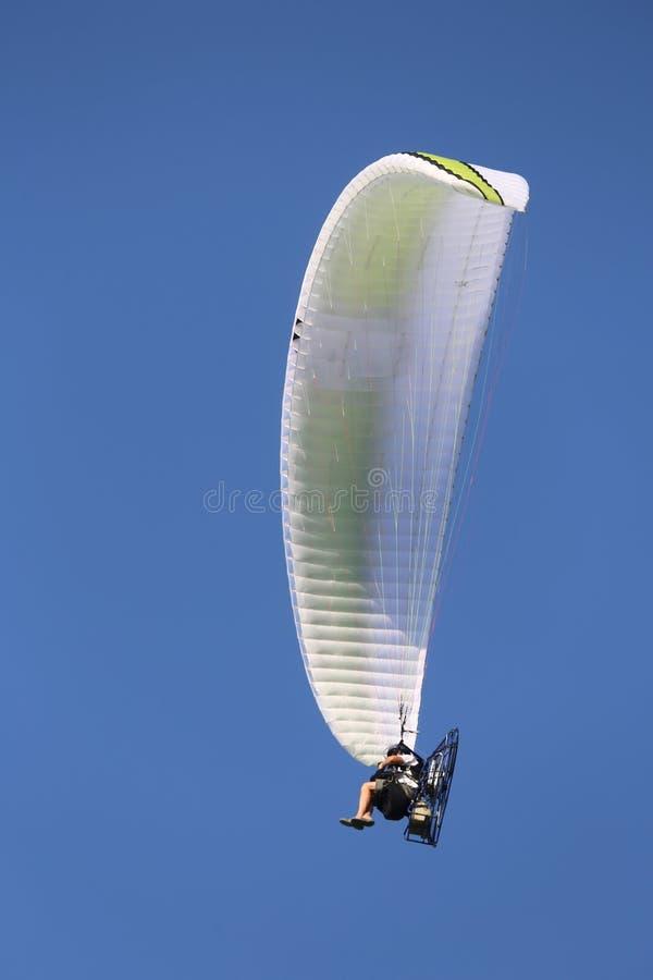 el planeador de caída accionado vuela arriba en el cielo azul con una persona se sienta fotografía de archivo