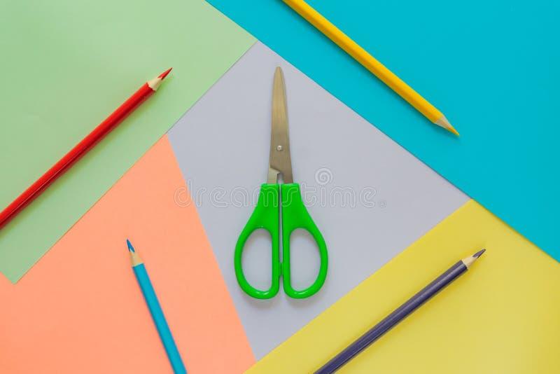 El plano creativo pone con los suppllies de la escuela lápices multicolores y scisors verdes en fondo colorido en colores pastel  imagen de archivo libre de regalías