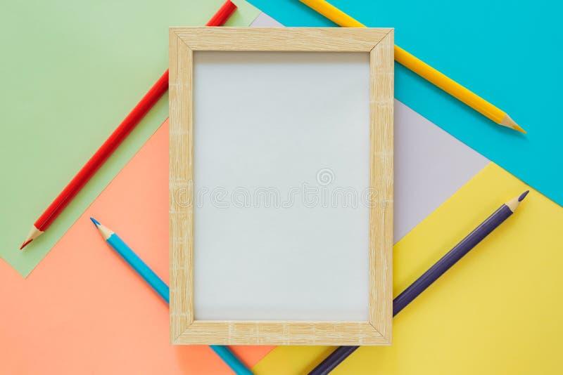 El plano creativo pone con los suppllies de la escuela Marco ascendente falso y lápices multicolores en fondo colorido en colores imagen de archivo