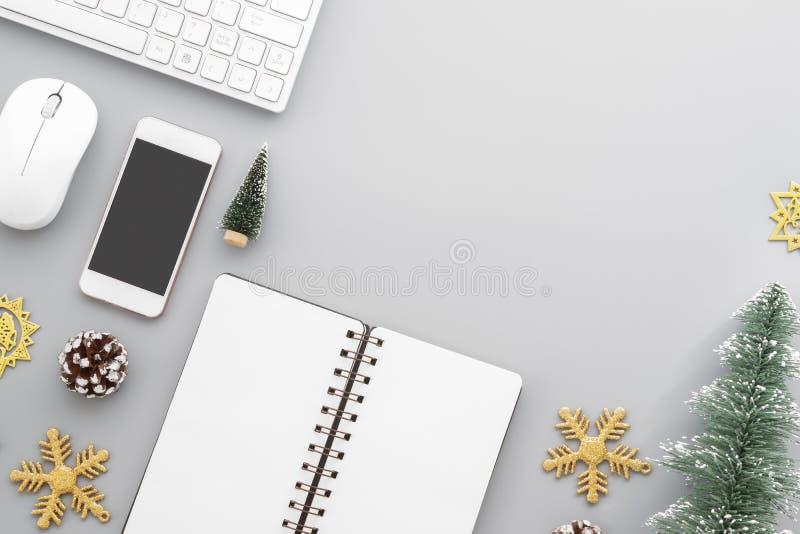 El plano de la tabla del escritorio de oficina de la Navidad pone con el teclado inalámbrico del ordenador, ratón, teléfono elega imagen de archivo