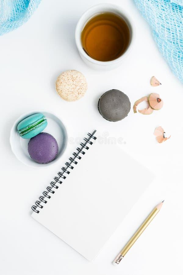 El plano de la visión superior pone la maqueta blanca en blanco del cuaderno con los macarons y la taza de té Arte, escribiendo c imagenes de archivo