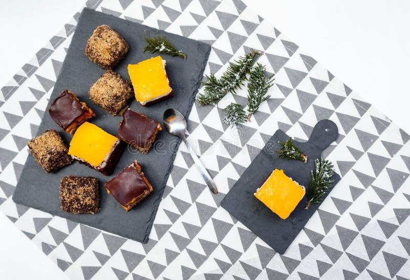 El plano de las tortas del chocolate, del caramelo y de las naranjas pone con el fondo divertido fotos de archivo