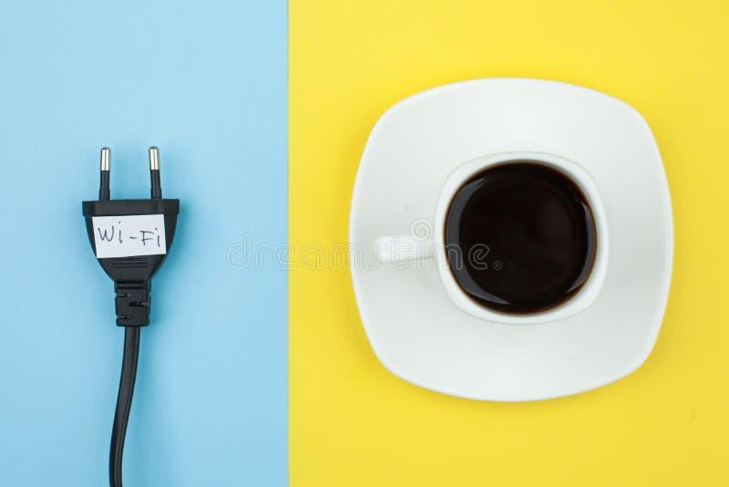 El plano de moda pone concepto mínimo, el cordón desenchufado con la palabra Wi-Fi y la taza del fondo brillante del café n, conc fotografía de archivo