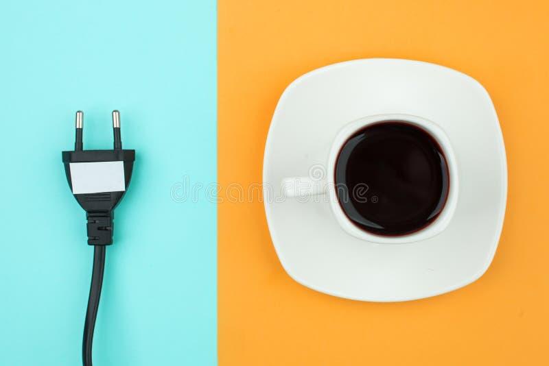 El plano de moda pone concepto mínimo, el cordón desenchufado y la taza de café en el fondo brillante, concepto de una rotura, re foto de archivo