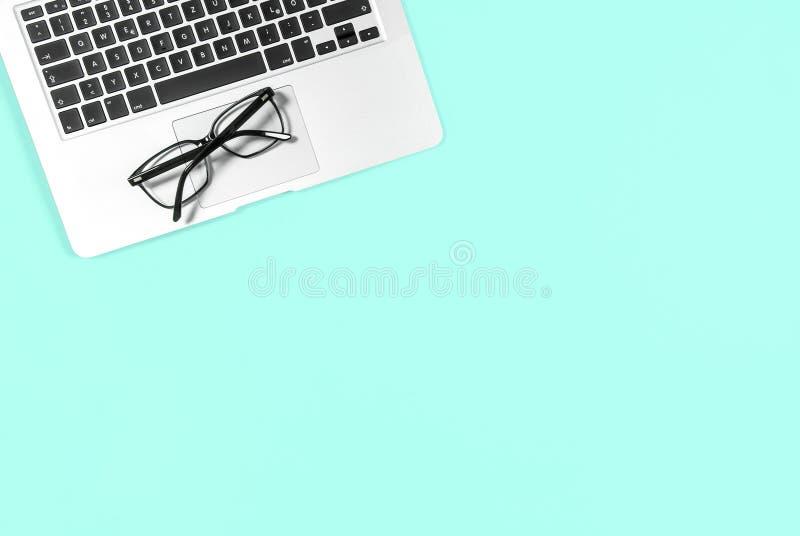 El plano mínimo del lugar de trabajo de la oficina pone los vidrios del ordenador portátil de la maqueta azules foto de archivo libre de regalías
