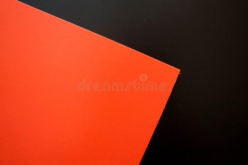 El plano oscuro pone el fondo con las hojas del papel del color Negro y rojo imagenes de archivo