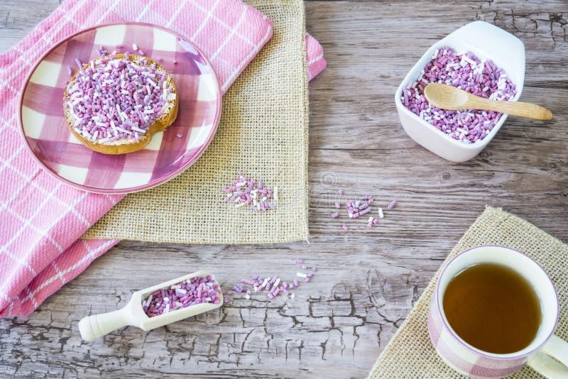 El plano pone con el bizcocho tostado, la p?rpura rosada dulce asperja y taza de t? Contra fondo de madera imágenes de archivo libres de regalías