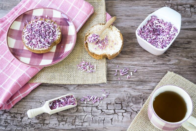 El plano pone con el bizcocho tostado, la p?rpura rosada dulce asperja y taza de t? Contra fondo de madera fotografía de archivo libre de regalías