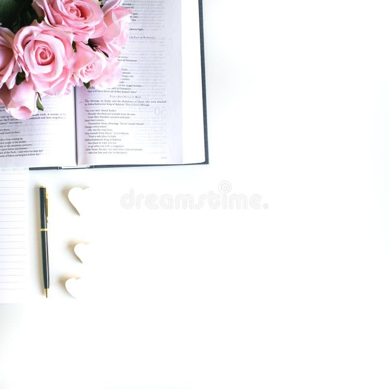 el plano pone con diversos accesorios; ramo de la flor, rosas rosadas, libro abierto, biblia imagen de archivo