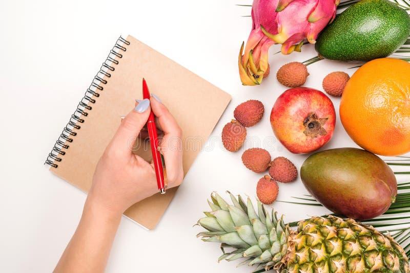 El plano pone con la fruta tropical y el cuaderno La mano de la mujer escribe plan de la dieta Lugar de trabajo elegante Dieta, f imagen de archivo