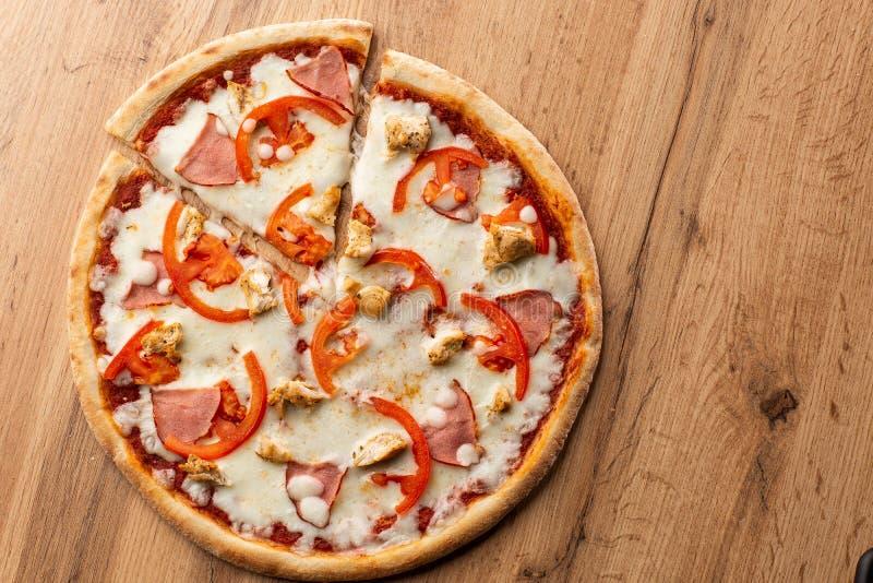 El plano pone con la pizza italiana tradicional con el pollo, el jamón, el queso y tomates en la parte posterior de madera fotografía de archivo libre de regalías