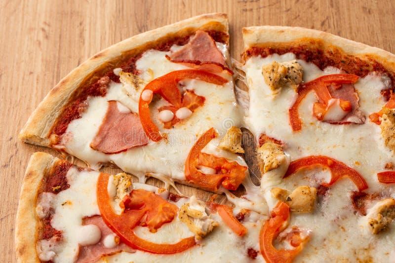 El plano pone con la pizza italiana tradicional con el pollo, el jamón, el queso y tomates en la parte posterior de madera foto de archivo libre de regalías