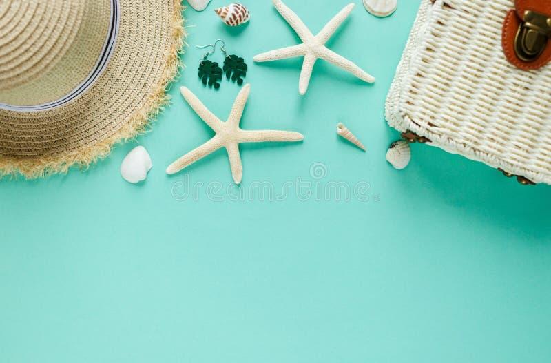 El plano tropical pone con el sombrero de paja, bolso, estrella de mar, cáscaras, pendientes en fondo verde La moda del verano pl foto de archivo libre de regalías