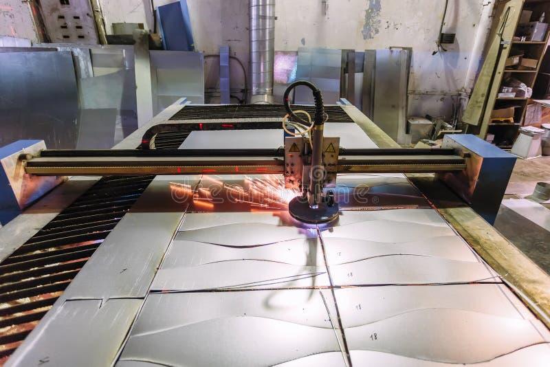 El plasma cortó la máquina con el control de programa que cortaba la hoja de acero con las chispas en fábrica de la trabajo de me foto de archivo libre de regalías