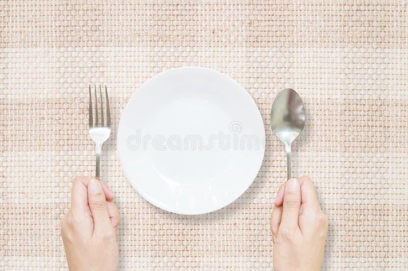 El plato de cerámica blanco del primer con la bifurcación inoxidable y la cuchara en mano de la mujer en la estera marrón de la t imágenes de archivo libres de regalías