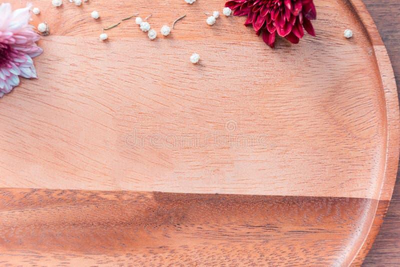 El plato de madera y las flores secadas tiraron en una cafetería foto de archivo