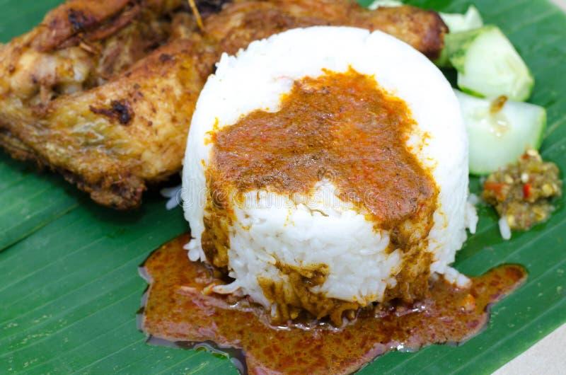 El plato malasio auténtico, arroz del vapor sirvió con la pierna de pollo, el pepino y la goma fritos del chile en la hoja del pl imagenes de archivo