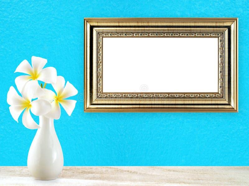 El plumeria blanco florece en el florero de cerámica blanco en piso de madera y el marco de oro del vintage en fondo azul de la p imagen de archivo libre de regalías