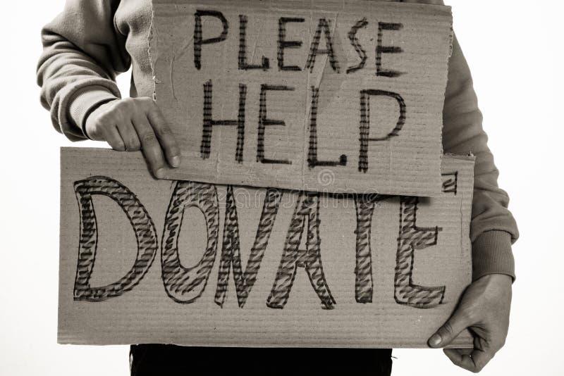 El pobre hombre sin hogar que lleva a cabo el tablero del cartón con palabra ayuda, DONA por favor fotos de archivo