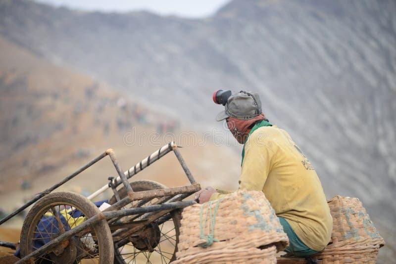 El pobre trabajador está sentado cerca del carro Minero imagenes de archivo