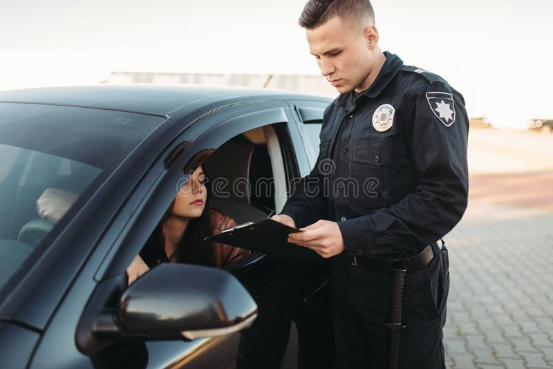 El poli en uniforme comprueba la licencia del conductor femenino imagen de archivo