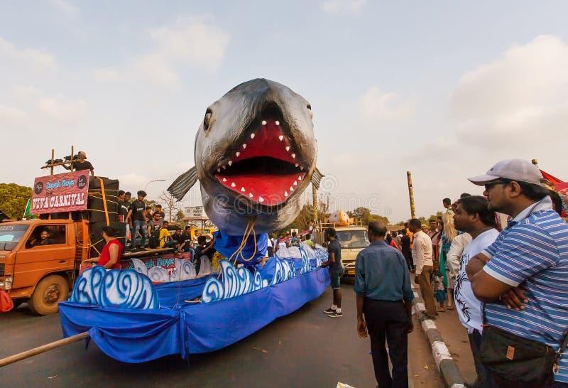 El policía acompaña a la procesión con las figuras de terroristas derrotados durante el carnaval tradicional de Goa imagenes de archivo