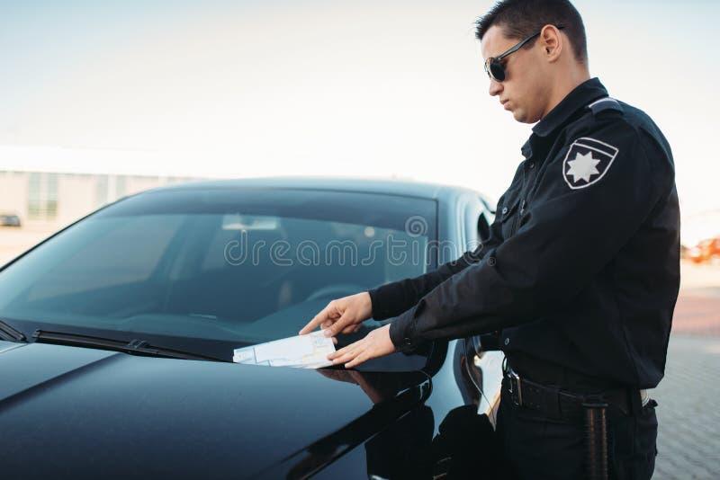 El policía de sexo masculino en uniforme escribe una multa en el camino imagen de archivo libre de regalías
