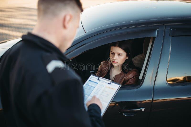 El policía en uniforme escribe muy bien al conductor femenino fotos de archivo