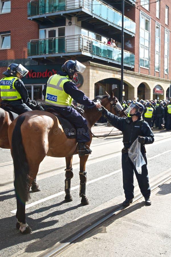 El policía montado recibe el agua fotografía de archivo