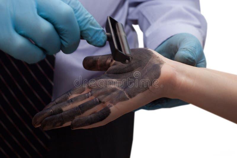 El policía toma huellas dactilares del sospechoso foto de archivo
