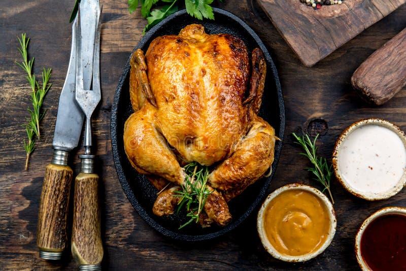El pollo asado con romero sirvió en la placa negra con las salsas en la tabla de madera, visión superior fotografía de archivo