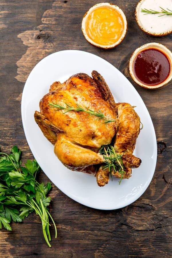 El pollo asado con romero srved con las salsas en la placa blanca, tabla de madera, visión superior fotos de archivo