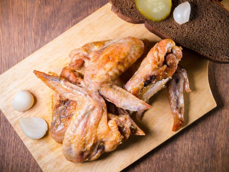 El pollo asado con una corteza curruscante miente en una tabla del postre con el pepino conservado en vinagre, pan imagenes de archivo