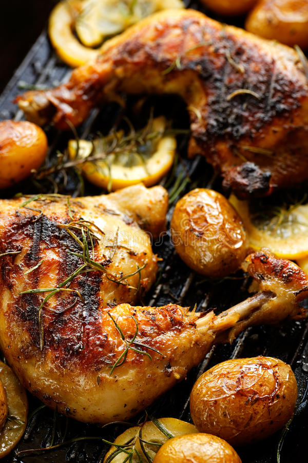 El pollo asado a la parrilla del limón del romero cuartea con las patatas asadas fotos de archivo