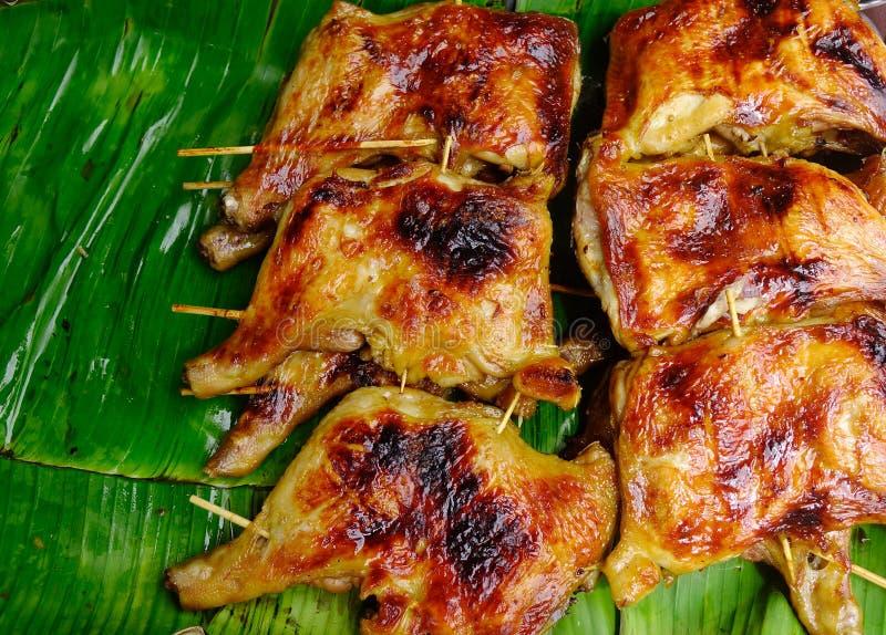 El pollo asado a la parrilla en plátano se va en el mercado rural imagenes de archivo