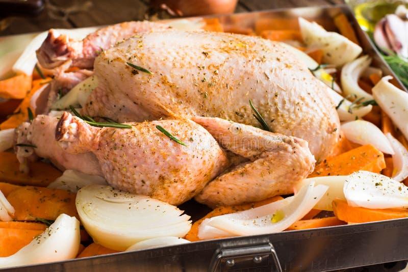 El pollo entero sazonó crudo en la bandeja con las cebollas tajadas de las patatas de las zanahorias de las verduras, romero de l foto de archivo libre de regalías