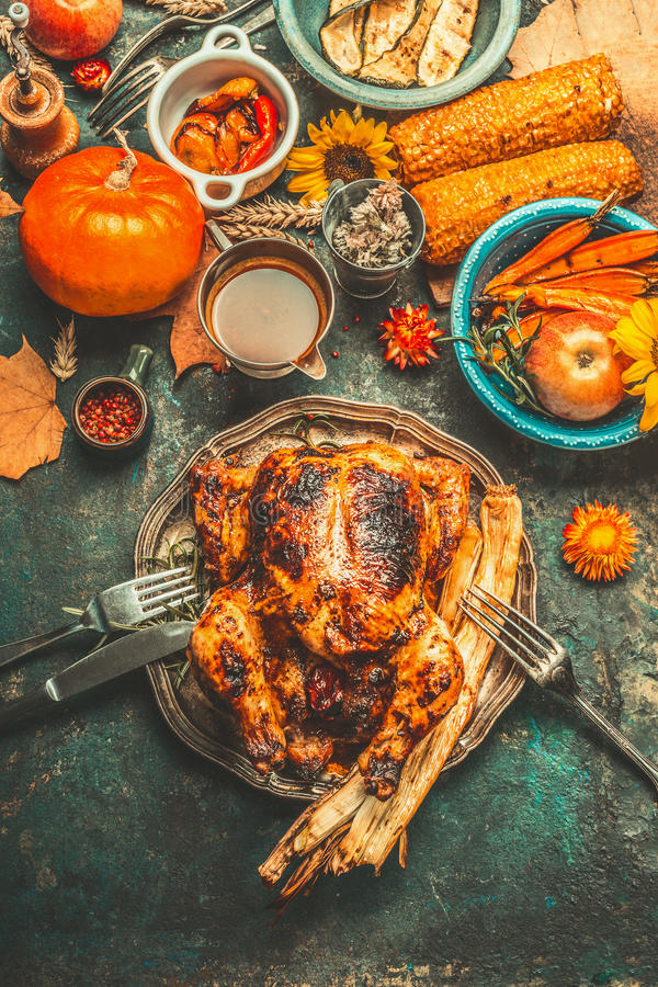 El pollo o el pavo relleno entero asado para la cena del día de la acción de gracias con la salsa, las calabazas, el maíz y el ot imagen de archivo