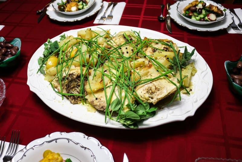El pollo y las patatas griegos del ajo del limón sirvieron en el disco blanco en el mantel rojo rodeado por los cuencos de ensala imagen de archivo libre de regalías