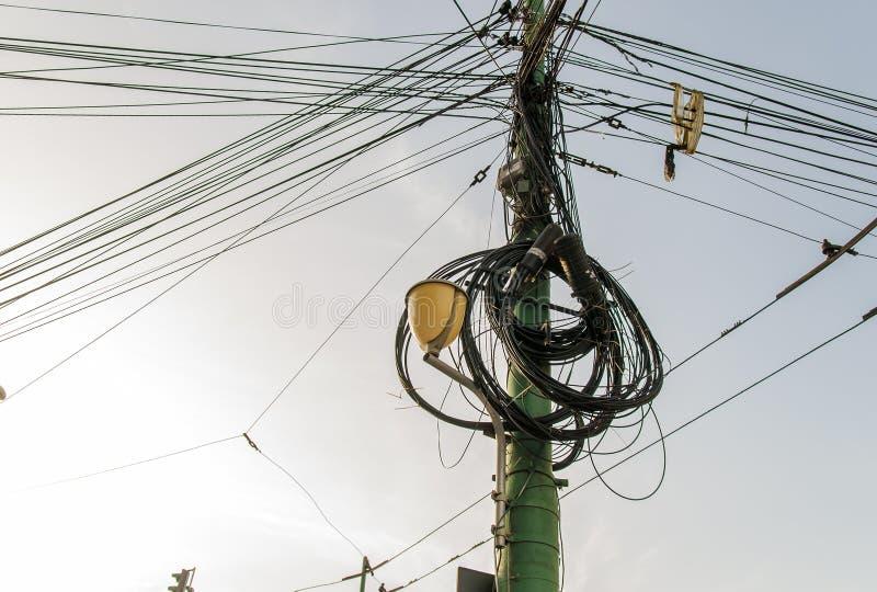 El polo de la electricidad y la luz de calle complicaron el cableado en el polo foto de archivo